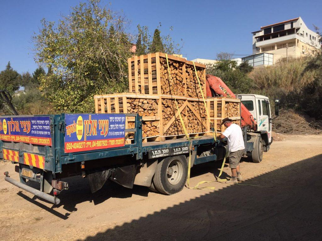 עצים להסקה על משאית עם מנוף